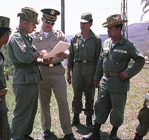 Foto de una película del ejército Estadounidense rodada en 1965. Los asesores militares de Estados Unidos se reúnen conel coronel Carlos Arana Osorio y un ayudante observa. De izquierda a derecha: el sargento Casper González,asesor de infantería EE.UU, elasesor de inteligencia delEjército de EE.UUMayorVernon Justice, un soldado guatemalteco no identificado, y el coronel guatemalteco Carlos Arana Osorio . Photo still from U.S. Army film shot in 1965. U.S. military advisors confer as Col. Carlos Arana Osorio and an aide look on.From left to right: Sgt. Casper González, U.S. infantry advisor; U.S. Army intelligence advisor Major Vernon Justice; unidentified Guatemalan soldier; and Col. Carlos Arana Osorio.