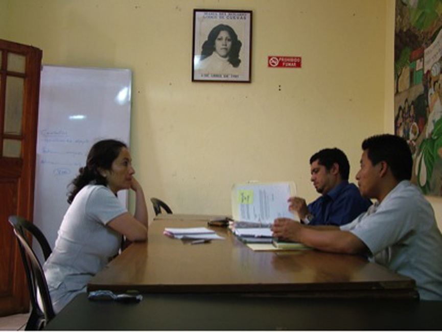 Ana Lucía Cuevas en una reunión de coordinación con Maynor Estuardo Galeano y Alejandro Axpuac, abogados del GAM.   Ana Lucía Cuevas meeting with lawyers from GAM, Maynor Estuardo Galeano and Alejandro Axpuac.    (Pictured on the wall behind, is Lucía's sister-in-law, and one of GAM's founders, Rosario Godoy de Cuevas.)