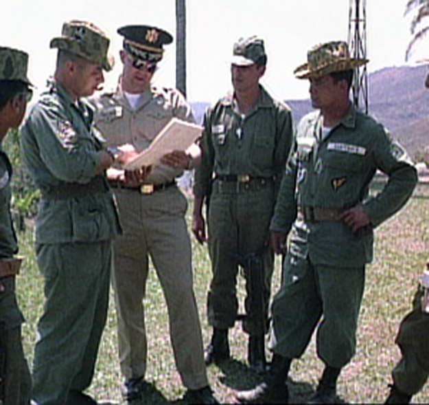 Coronel Carlos Arana Osorio y su ayudante se reunen con asesores del ejérito Estadounidense (1965) U.S. military advisers confer as Col. Carlos Arana Osorio (on the right) and an aide look on (U.S. Army, 1965)