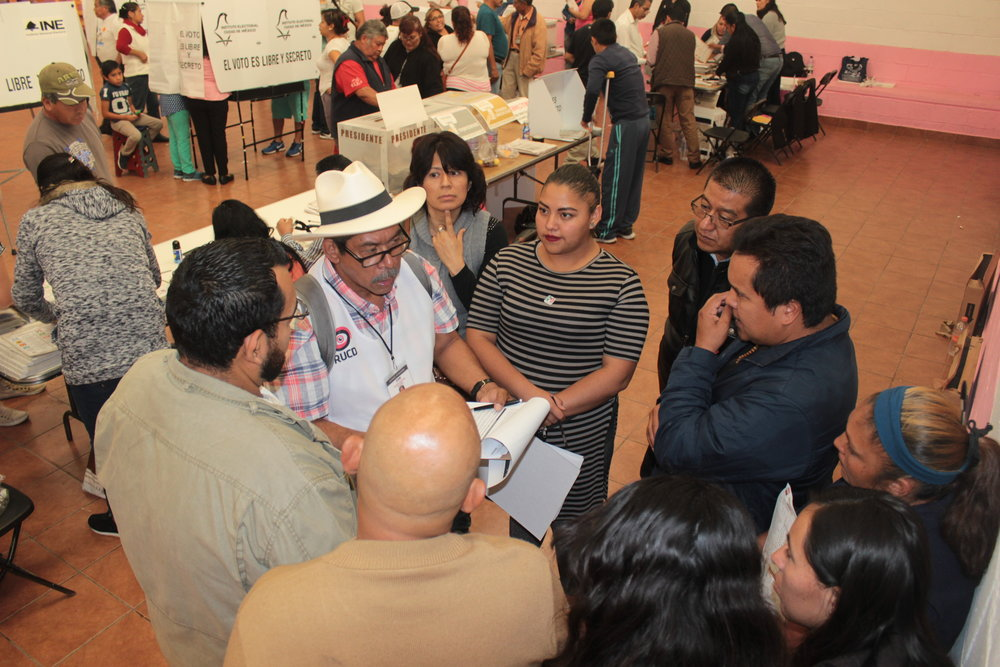 International Observer Brigade No.10 member, Carlos Cruz, interviews party representatives observing the voting at 'Casillas' Modelo de Bienestar Social, Mexico City, as to their views on the fairness of the process they had been observing all day.