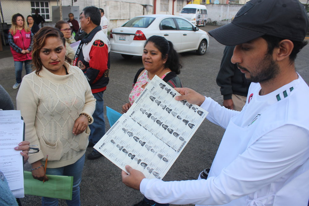 David Gonzalez Islas (right) inspecting the voter registers, alongside Mexican volunteers outside Jardin de Niños John Dewey infant school, Estado de Mexico