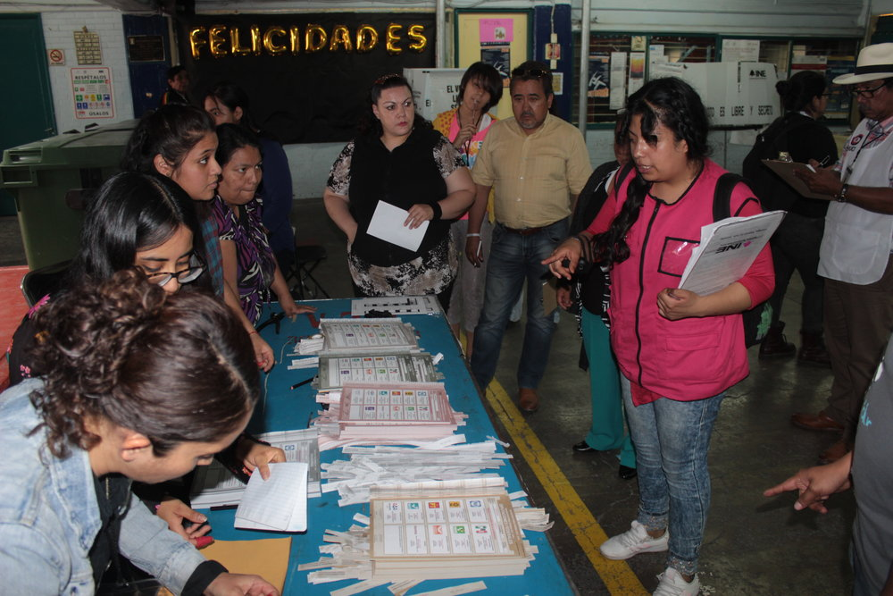 An electoral commission (INE) representative re-iterates to local volunteers the procedures for the beginning of the 'count'. She, and the other volunteers who had worked the whole day monitoring the vote, were still being 'overseen' by representatives of the competing political parties, now behind the closed and locked doors to the voting station at Escuela Secundaria 7 JMR.