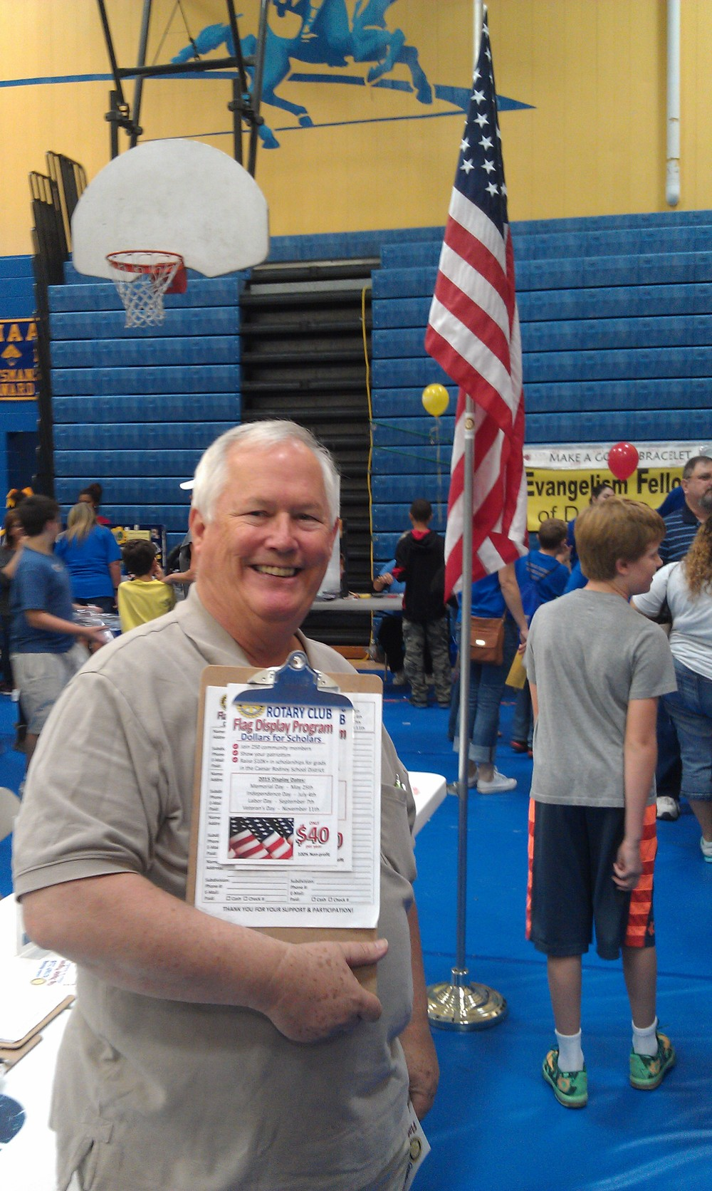 Camden-Wyoming Rotary Club member, John Kirby, at the Caesar Rodney High School Rider Pride Day event.  With a flyer for the Flag Display Program and sign-up sheet in hand.   Photo by club member Troy Cooper.  (not pictured, club member Steve Welde)