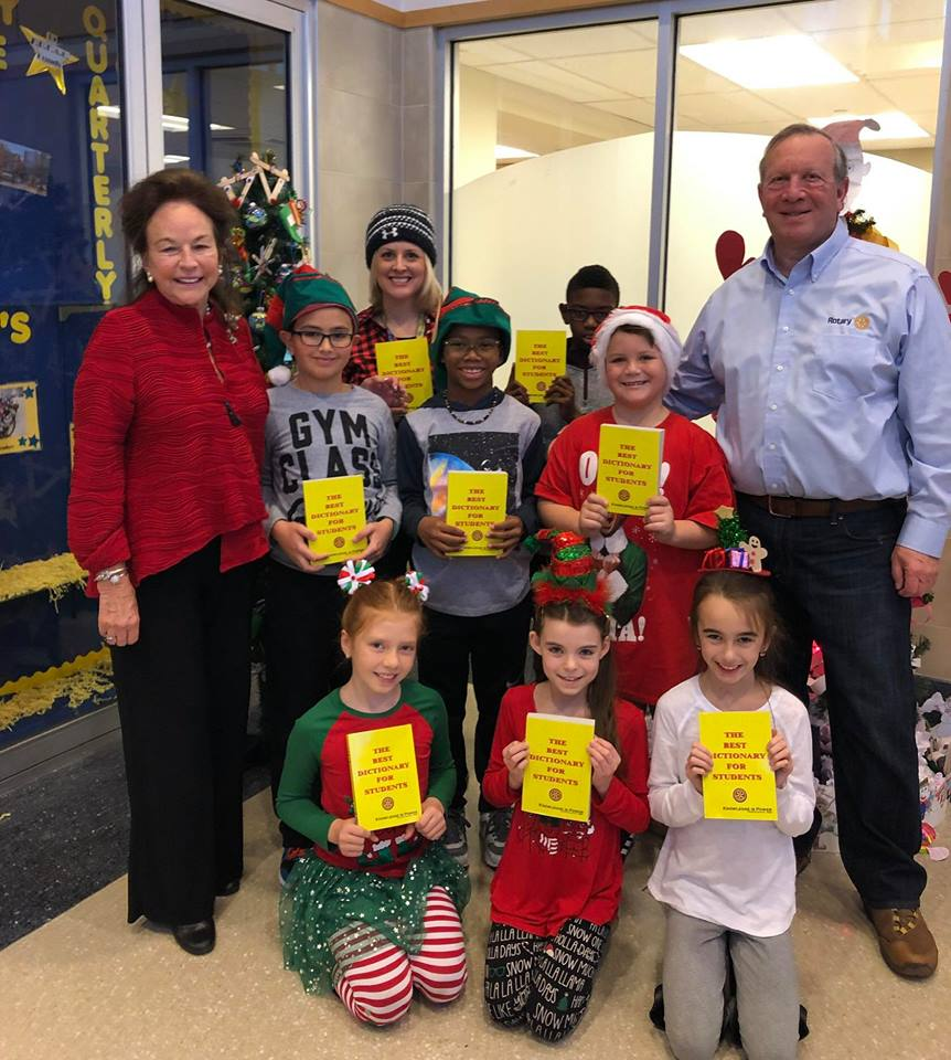 Club President Trish Rodriguez (left) and Club Member Ron Kahn (right) posing with 3rd graders and their new dictionaries.