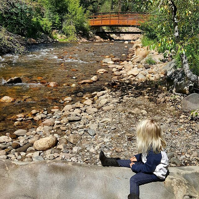 Down by the river.  #nature #colorado #fallriver #river #rock #toddlertravel #boots #rockymountains #blonde #bridge #🤠 #☀️