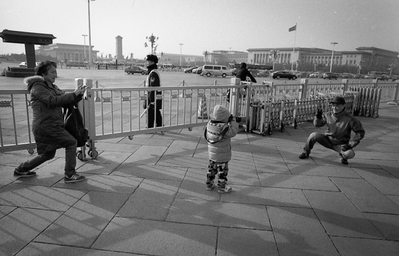 Child plays with a camera in Tiananmen Square