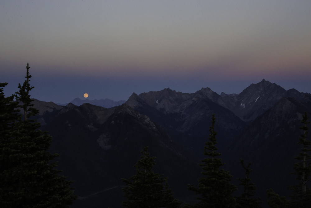 The blue moon rises over the rockies as Fischer Mountain thrusts skywards.