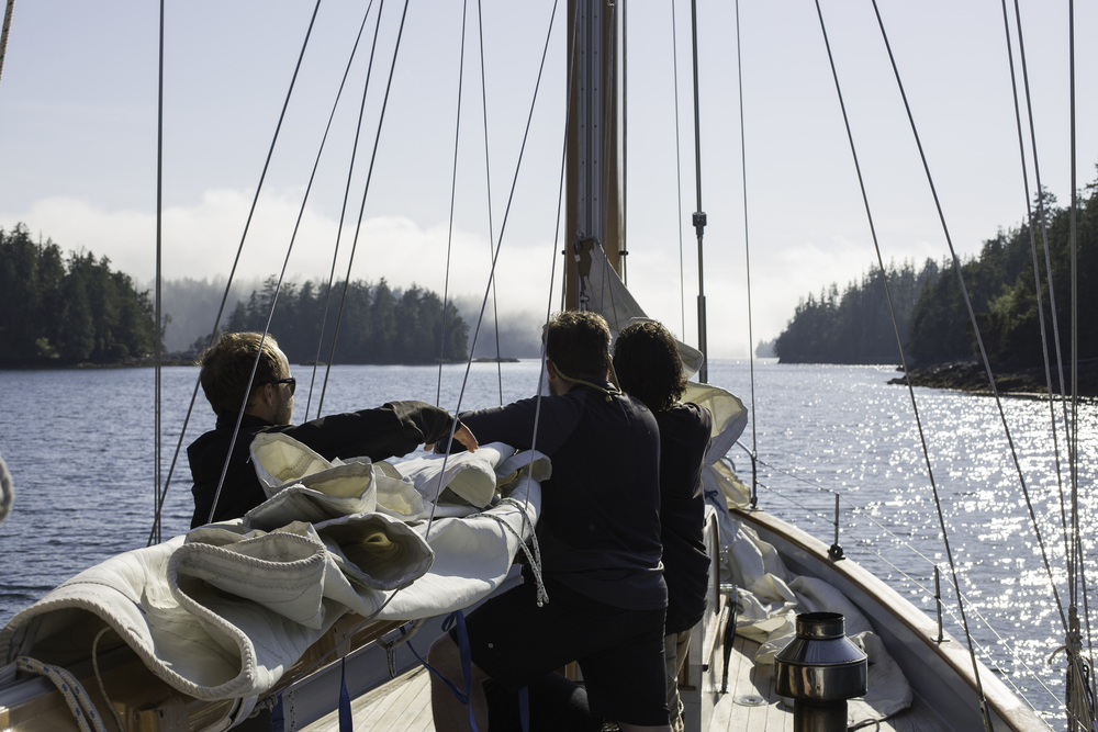 "Captain Matt Lemay shows first mates Joel White and Liam Ogel the appropriately named ""Burrito Technique"" for wrapping up the sails."