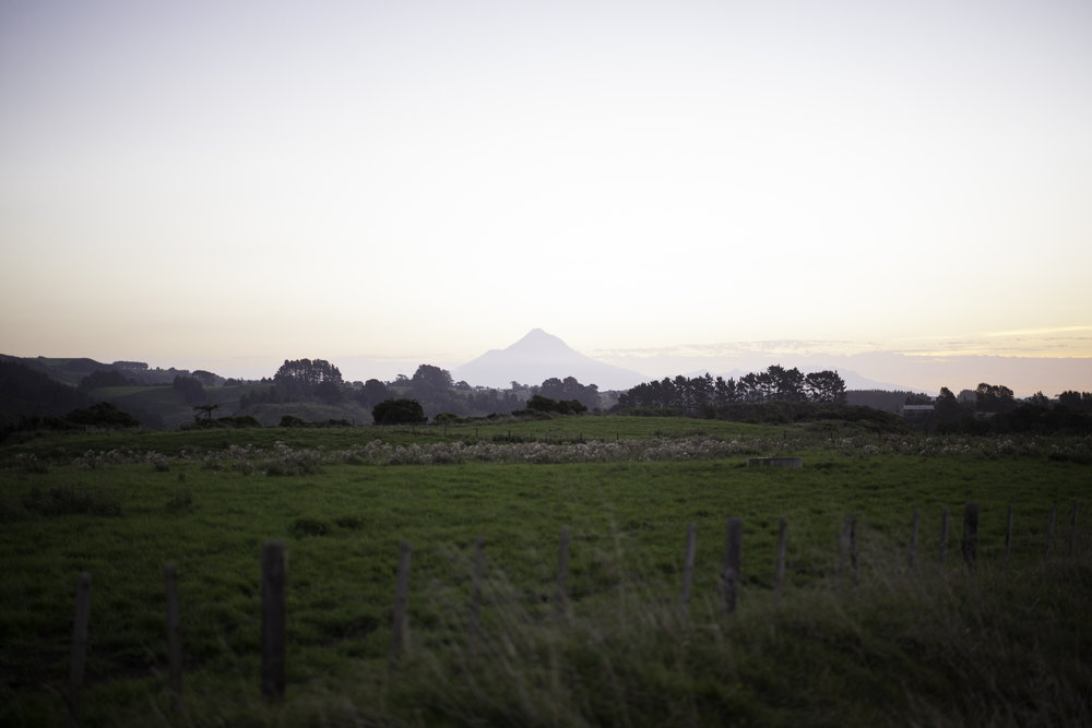 Mt. Taranaki is to the surrounding farm fields as rock pinnacle is to a flat ocean floor. Visible.