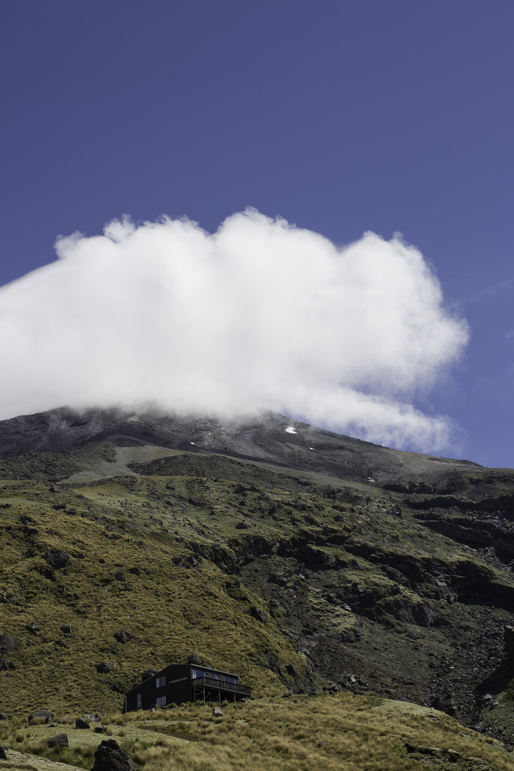 The hut mirrors the shape of the perlan clouds pouring over the top of Mt. Taranaki.