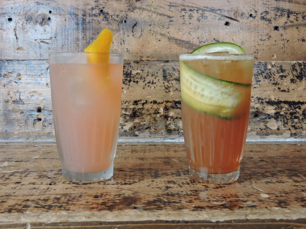 """On the right: The firing squad - Reposado tequila, lime, brenadine, ginger beer, angostura, orange swath    On the left: Patio Cup - Pimm's no.1, deaths door gin, """"home brew"""" , strawberry, ginger, lemon, cucumber, black pepper"""
