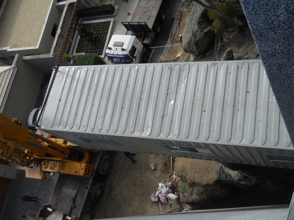 Container being hoisted into position