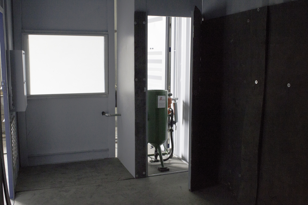 Inside of Sand Blasting container showing blast pot