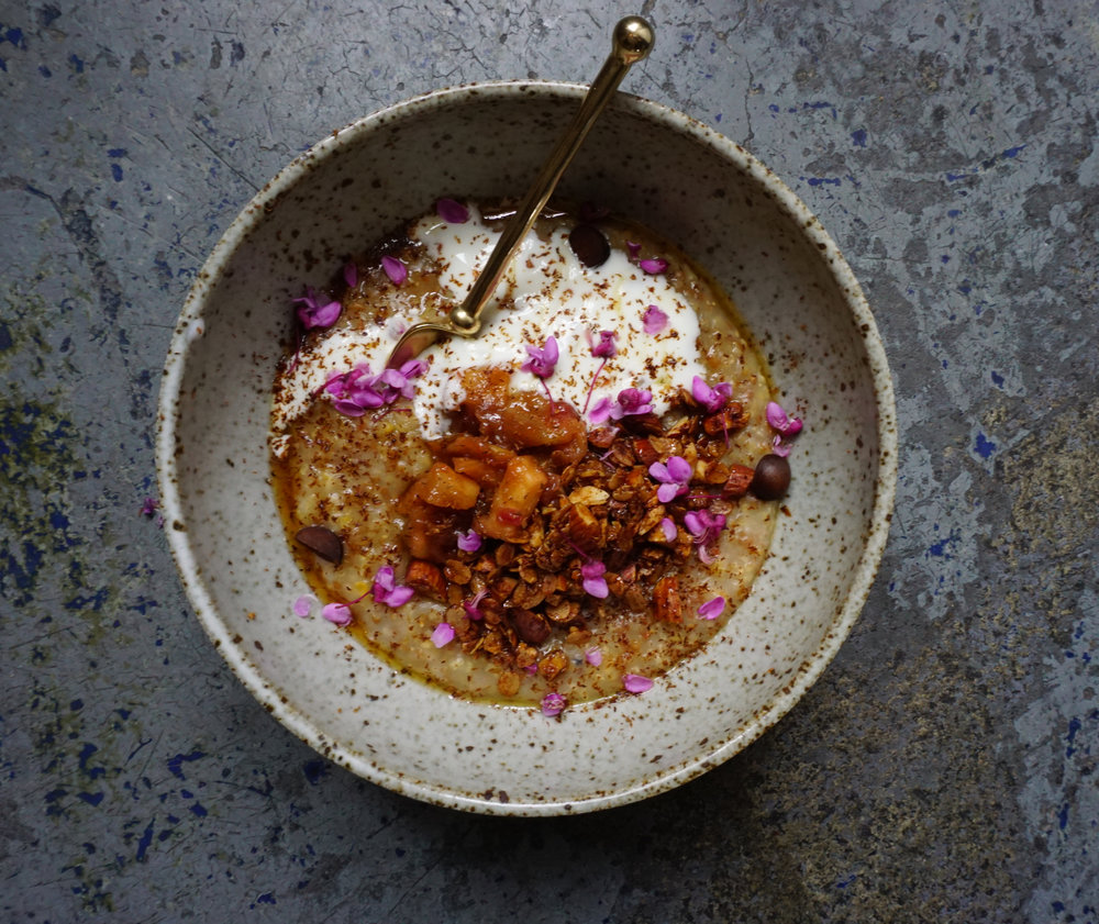 Heirloom grain porridge with feral rhubarb(!) crisp, cardamom, yogurt, maple syrup, bay nut, and red bud flowers.