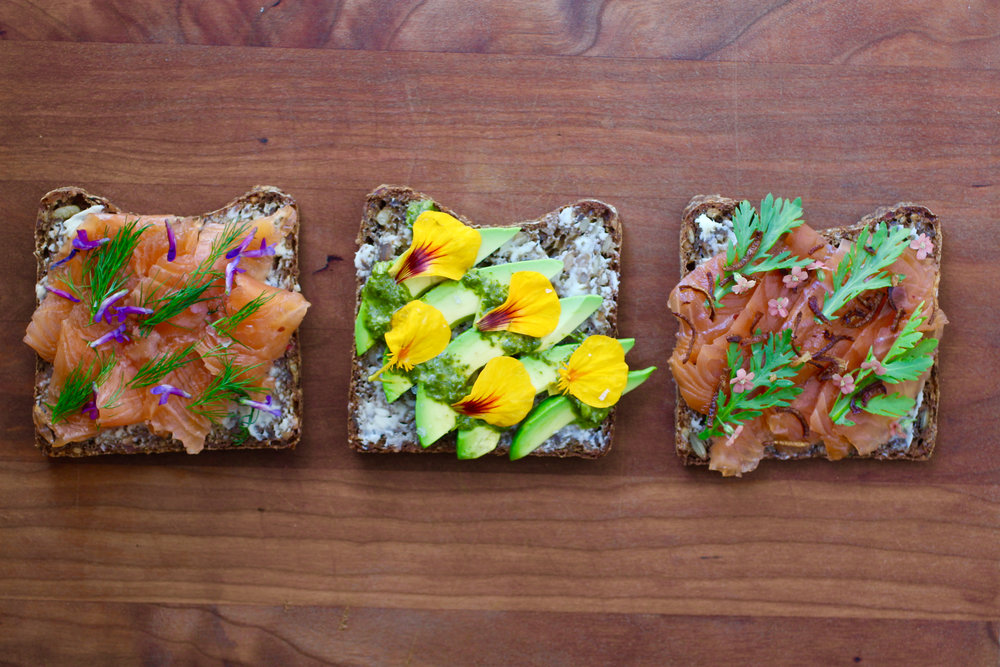 Smørrebrød topped with gravlax, dill, and foraged vetch flowers; avocado and nasturtium; and gravlax, crispy shallot, yarrow, and chrysanthemum.