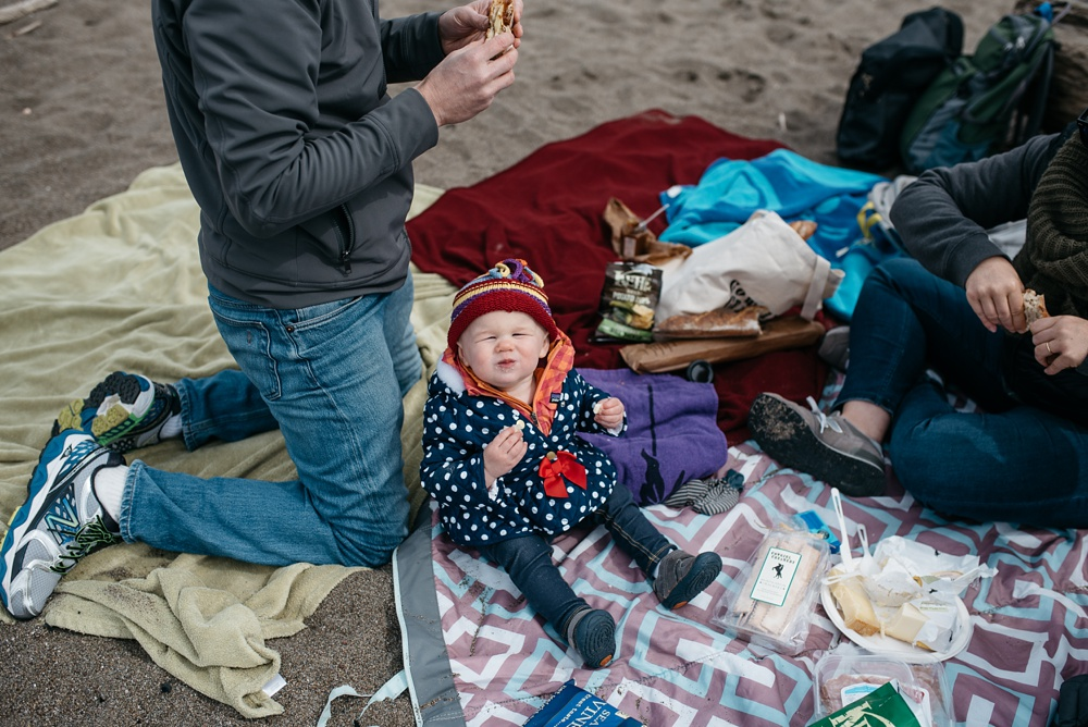 A young family picnics at South Beach at Point Reyes National Seashore in California. Family travel portrait photography by Sonja Salzburg of Sonja K Photography.