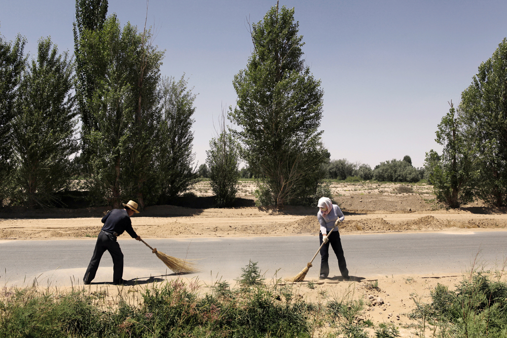 Outside an abandoned village to Chinese construction workers are clearing a country road before it gets a new coat of asfalt. The increasing desert storms cover the roads and hinders traffic on the road leading to Inner Mongolia.