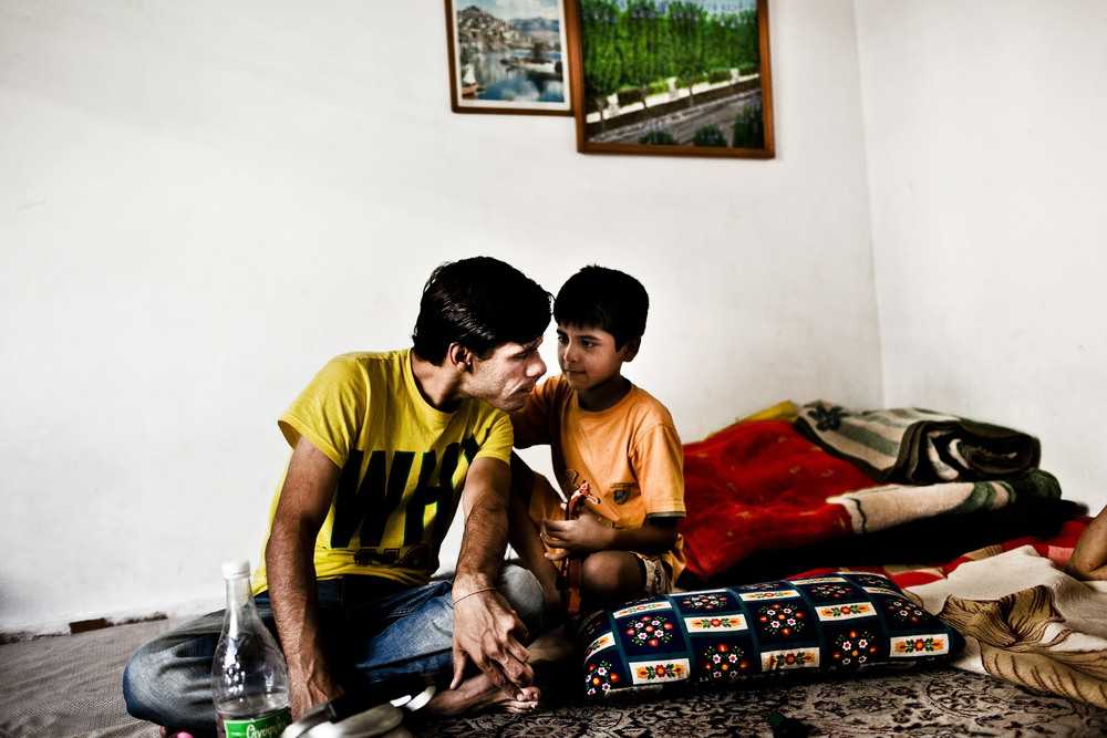 Two young refugees exchange music in a so-called Afghan Hotel, an overpriced rental flat for refugees. Hamed fled as an unaccompanied refugee but the little boy is travelling with his father and brother and they hope to reunite with the mother in Germany. 17 year old Hamed left Afghanistan at age 15 and doesn't want to seek asylum in Greece. His family took a 5000 euros loan - money that they now owe the neighbor to get Hamed to Europe. He lives on the roof of an abandoned building in Alexandra Park in Athens.