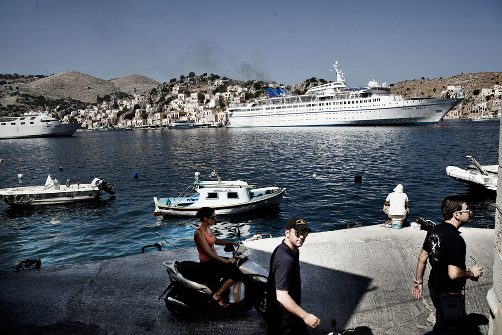 Frontex personnel cross the pier while a cruise ship go about its usual business. The local detention has a capacity of 10 persons but holds over 100 boat refugees who crossed the Aegean Sea in overloaded inflatable rafts. The detention conditions are poorly with strained toilet facilities and limited space on Greek tourist island Simi.