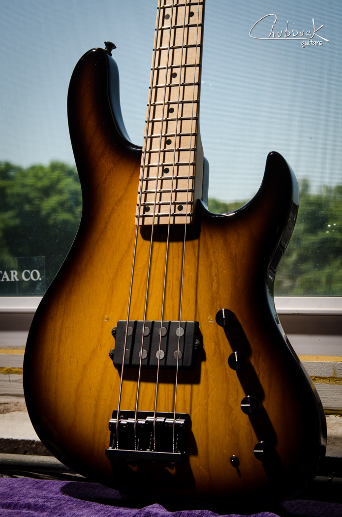 2008 Sadowsky Modern 24 Music Man :: set up and pickup cover holes plugged. Sadowsky consistently makes some of the finest basses to grace my bench.  This one is a super lightweight ash body and sounds absolutely huge.  The controls and preamp offer a wide variety of tones.  From top to bottom: passive volume, active volume, bass cut/boost, treble cut/boost and a mini toggle for series/split/parallel.  The passive and active volume controls allow you to blend between the straight and buffered signal - extremely versatile!  And I can't get over how lightweight yet balanced this bass is. The setup is super low on this one - similar to the action found on an electric guitar.  The player installed a bridge cover at one point and has since removed it.  I plugged the holes and matched the color of the center sunburst with tinted shellac.