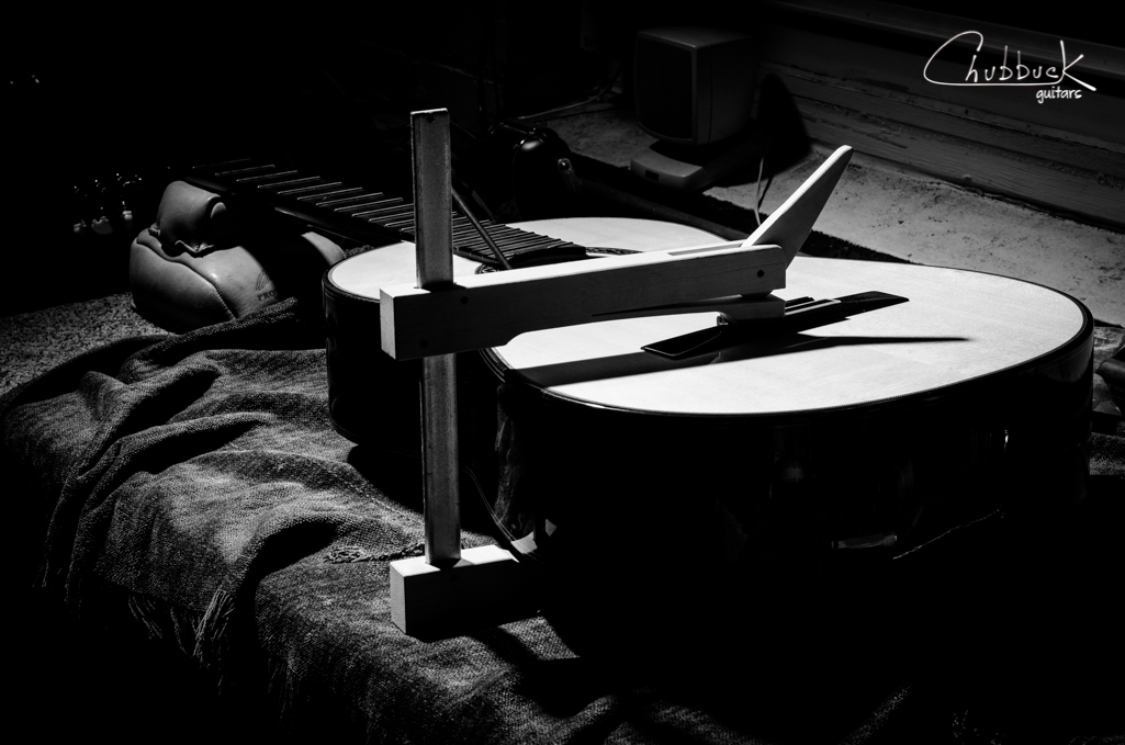 Classical guitar back repair :: gluing up loose back braces (4 of 5) before gluing the severe crack that runs the length of the body. The trick with this one is to add just enough moisture to close the crack, yet not too much as to cause the joint to overlap or bind.