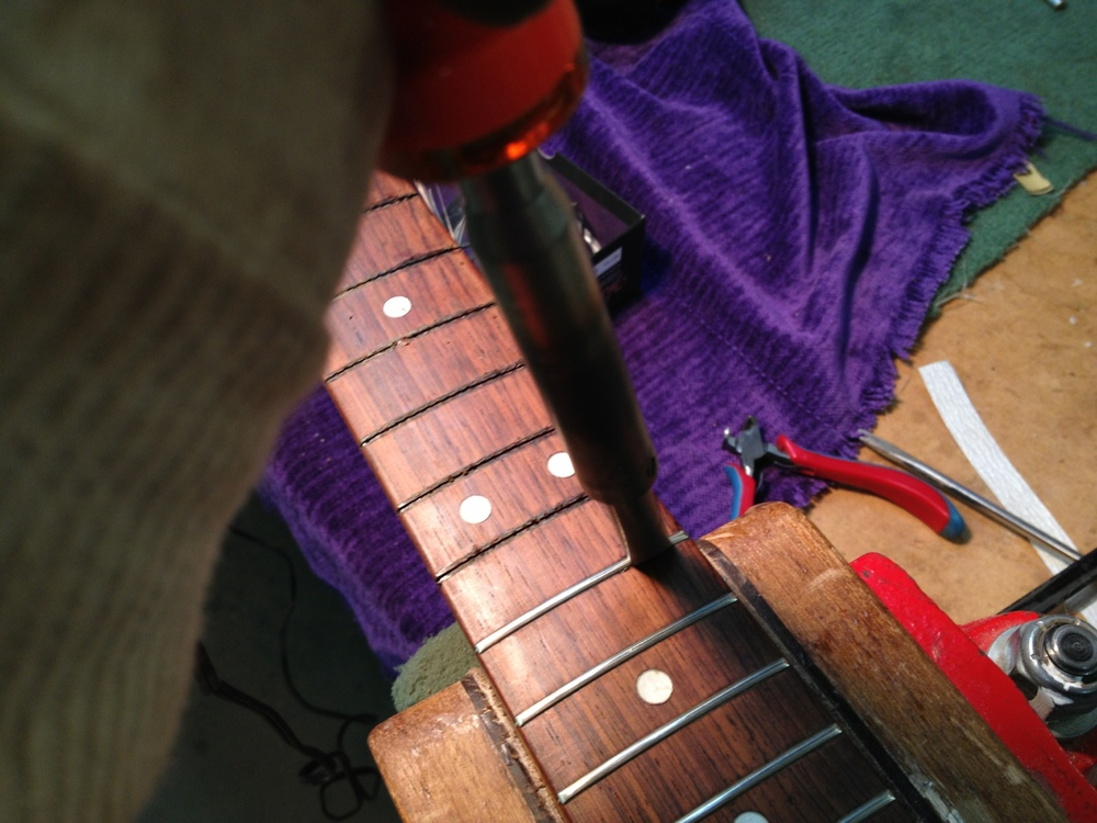 Heat applied to loosen frets for removal