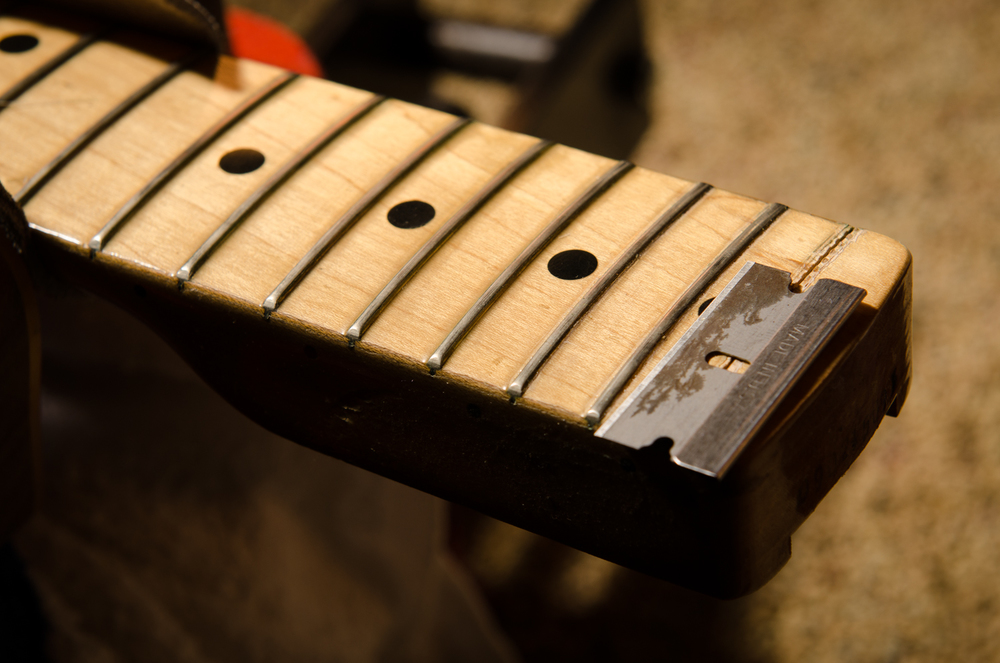 The original frets are installed pre-finish, so there is a thick polyester web that seals the frets in. This web needs to be completely cut-through in order to prevent damage to the surrounding fingerboard finish. This is a long and meticulous process to ensure each fret is fully disconnected from the fingerboard finish prior to removal. Another trick is to tighten the truss rod before removing the frets. This springs opens the fret slots slightly to help minimize chip-out.
