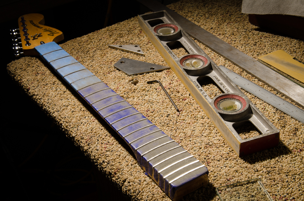 The truss rod is adjusted as straight as possible and the frets are level sanded. Note that the body end of the fingerboard is being sanded more than the rest of the board. There is a slight body hump and these frets will have to be sanded a little more aggressively than the others. Not a problem if I was able to sand the maple board itself and properly prep it for frets, but we are keeping the original finish and this is the compromise. Here's where the higher crown frets help.