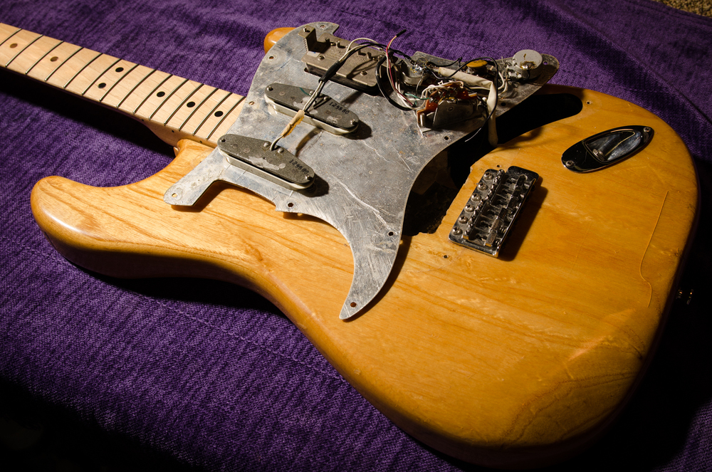 The bridge humbucker will be disconnected and removed. Then the remaining components are ready to be transplanted to the replacement pickguard.