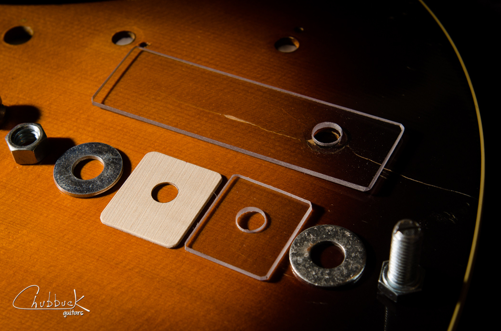 Here is the breakdown of the clamping setup. It assembles from right to left. Bolt, washer, small plexiglass and maple reinforcement go inside the guitar. Large plexiglass, washer and nut go on the outside.