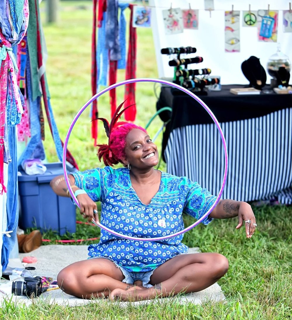 Beaming Janelle in front of her jewelry booth at a hula hoop festival [Photo by Red Light Photos]