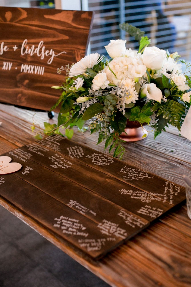 White and green wedding flowers with custom wooden sign in book