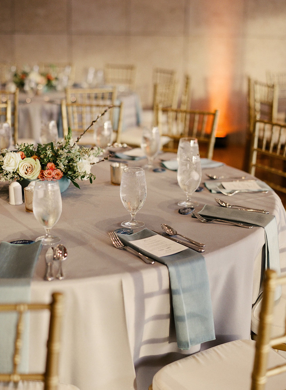 Modern wedding table with grey linen, french blue napkin and colorful floral centerpiece