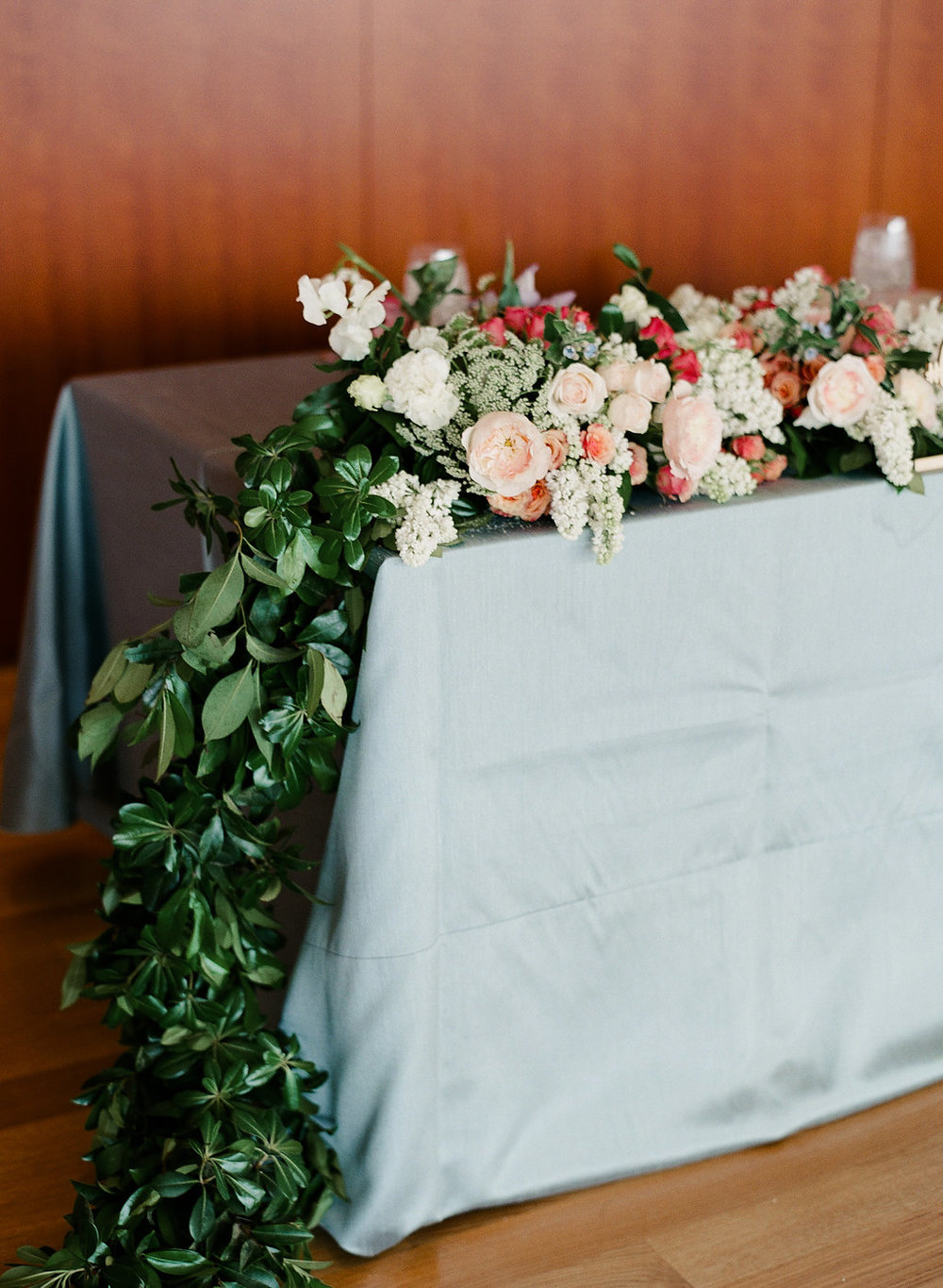 French blue linen on rectangular sweetheart table with floral garland