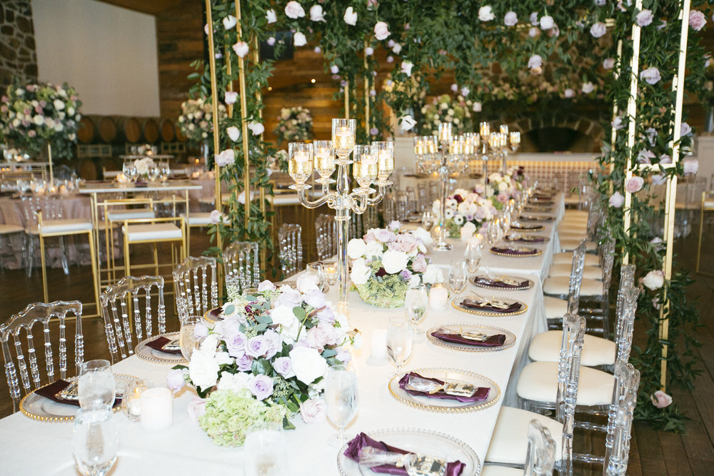 Lush floral canopy with blush linens, glass beaded chargers, and crystal candelabras