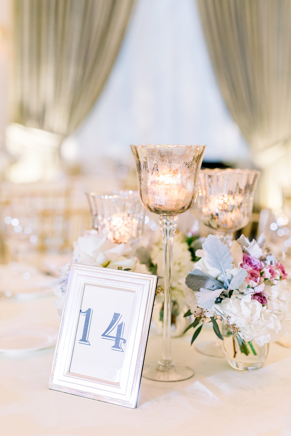 Blue and gold table numbers, trio candle centerpiece with floral