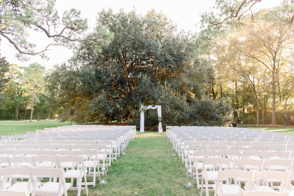 Outdoor wedding in front of the Houstonian Tree with a wooden arch, draping and floral arrangements