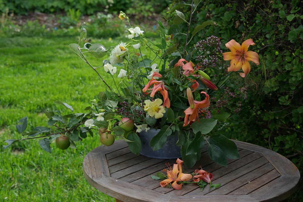 A garden arrangement of lilies, apple branches, nicotiana, nasturtium, oregano, calendula, 'Frosted Explosion' grass and poppies