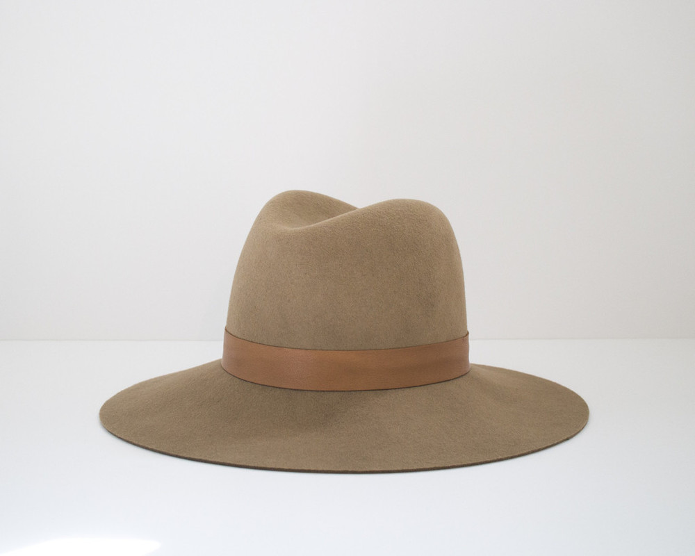 "It's not hard to fall in love with Janessa Leone's line of hats. They're sleek, cool and she adds special metallic touches to many of them. This classic camel colored ""Clay"" hat features a lambskin leather band and gold screw closure."