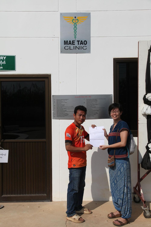 工作人員 Khun Way 代表梅道診所,將捐款收據交給 Glocal Action 企畫經理王詩菱。