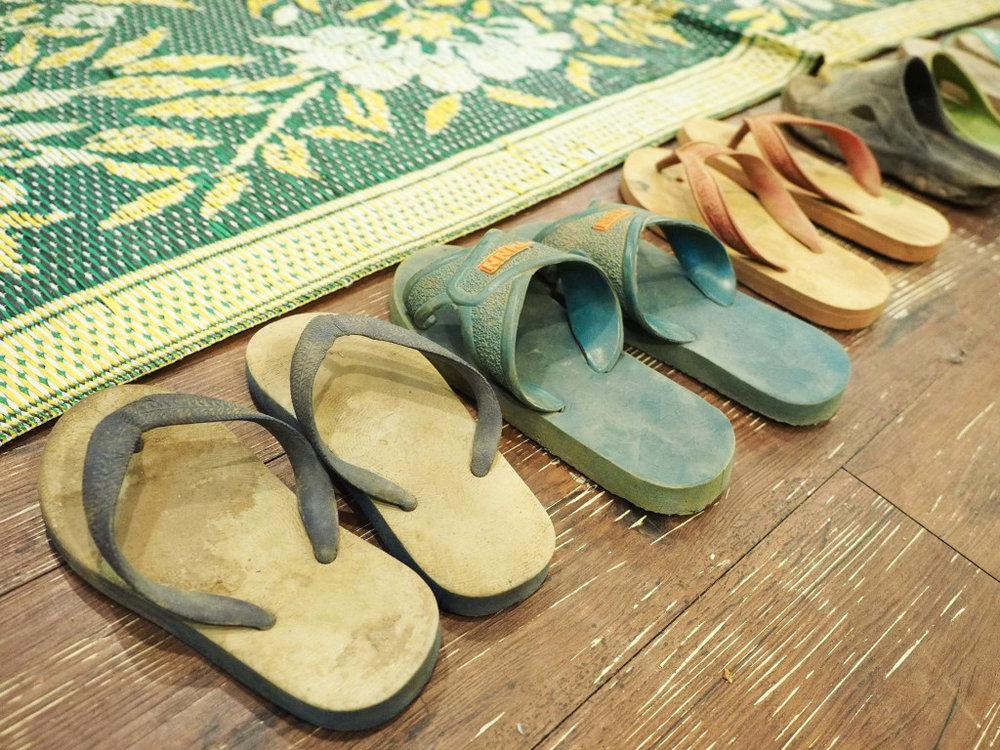 當地孩童大多穿著拖鞋上學,進入教室時就將鞋子脫在座位旁邊。圖/張家銘