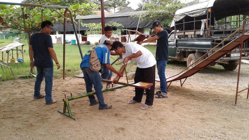 新浪潮小學 Saw Htat 校長、我們的當地夥伴 TBCAF 工作人員、兒童藝術教育課程Wana Zaw 老師、廠商工人,同心協力組裝遊樂器材。(攝影╱王詩菱)
