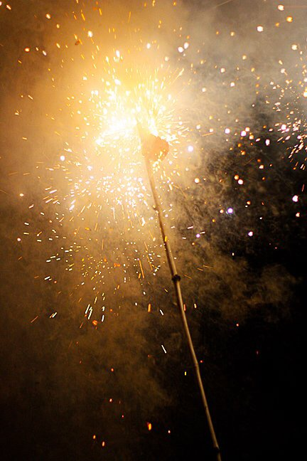 Exploding firecrackers, strung from a bamboo pole. Photo by  Nicolas Los Baños