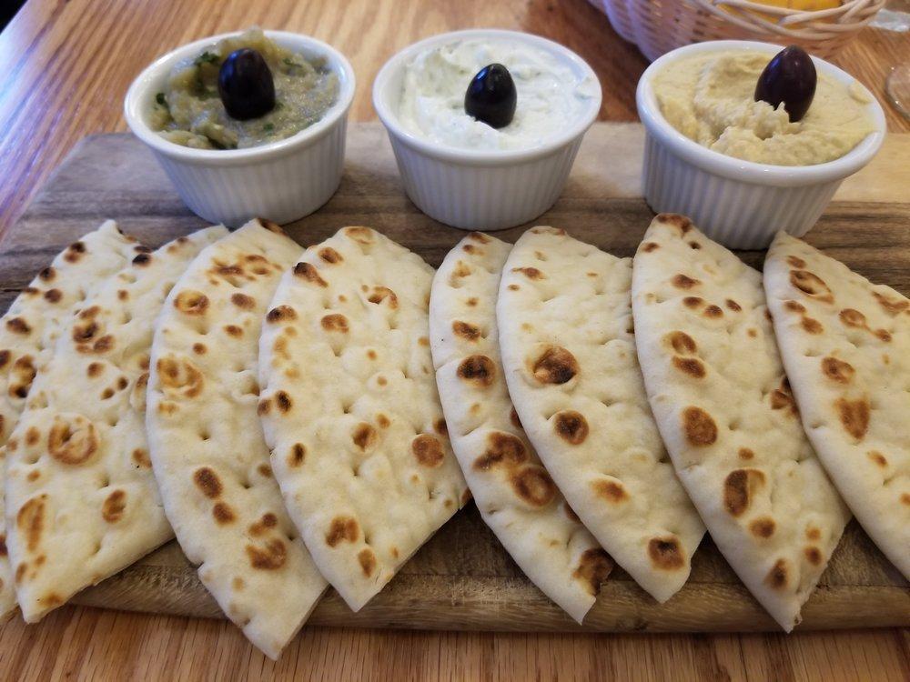 From left to right: Melitzanosalata, Tzatziki, Lemon Hummus, and the pita, of course.