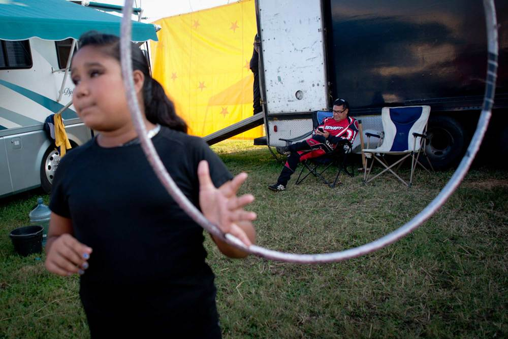 Belgica Perez, 11, (left) practices with the hula hoop while Oscar Garcia, the owner of the circus, checks his email before the show. The circus travels in four RVs that they park in a circle to create a semi-private space behind the stage for practice and relaxing between shows.