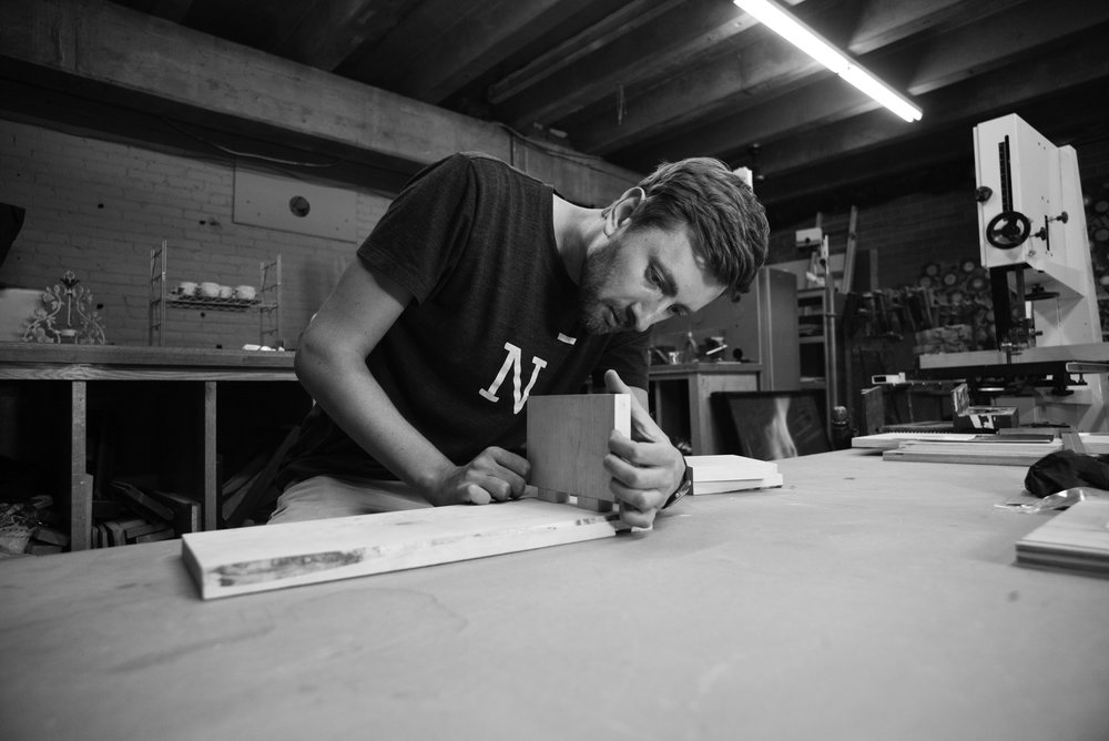 Processus Member Ivan Pantoyev working on wood bench