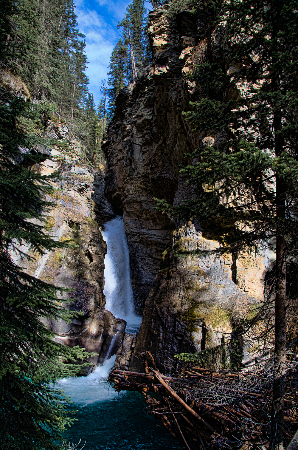Falling Through The Canyon. Johnston Canyon is located in Banff National Park, Alberta, Canada. This was such a neat area to walk through. This is the lower falls, which is still a nice little hike to get to. Maybe next time we will keep on hiking to the next falls.