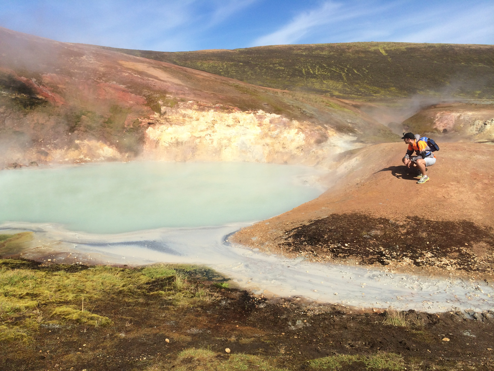 A man admire a blue/green-colored hot spring