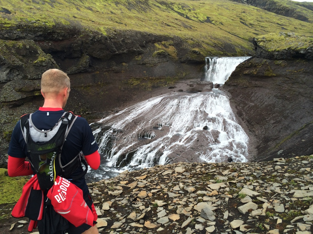 A runner taking a pause and watching a small waterfall