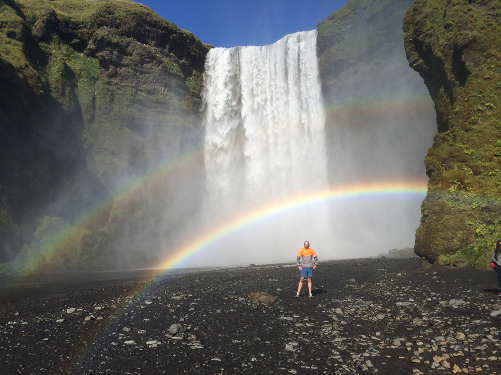 A man, rainbow and Skogafoss